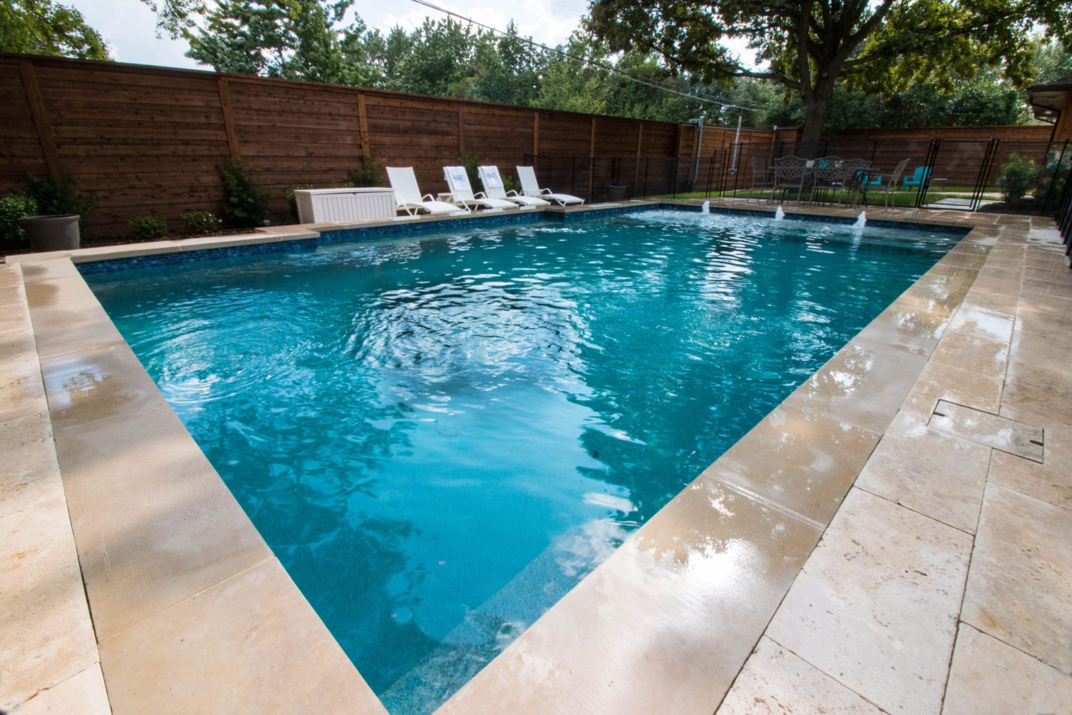 overview of the swimming pool with the ivory travertine pavers by qdi splash pad and bubblers