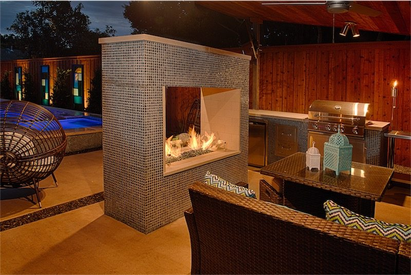 "Of the many immaculate design features of this backyard, we are always stunned by the complexity and beauty of this outdoor fireplace. This feature is constructed of hand laid 1""x1"" tile pieces and includes a rectangular fire system. Complimented by 1/2"" reflective fire glass this fire pit is design to illuminate every ray of light to provide both warmth and awe to its viewers."