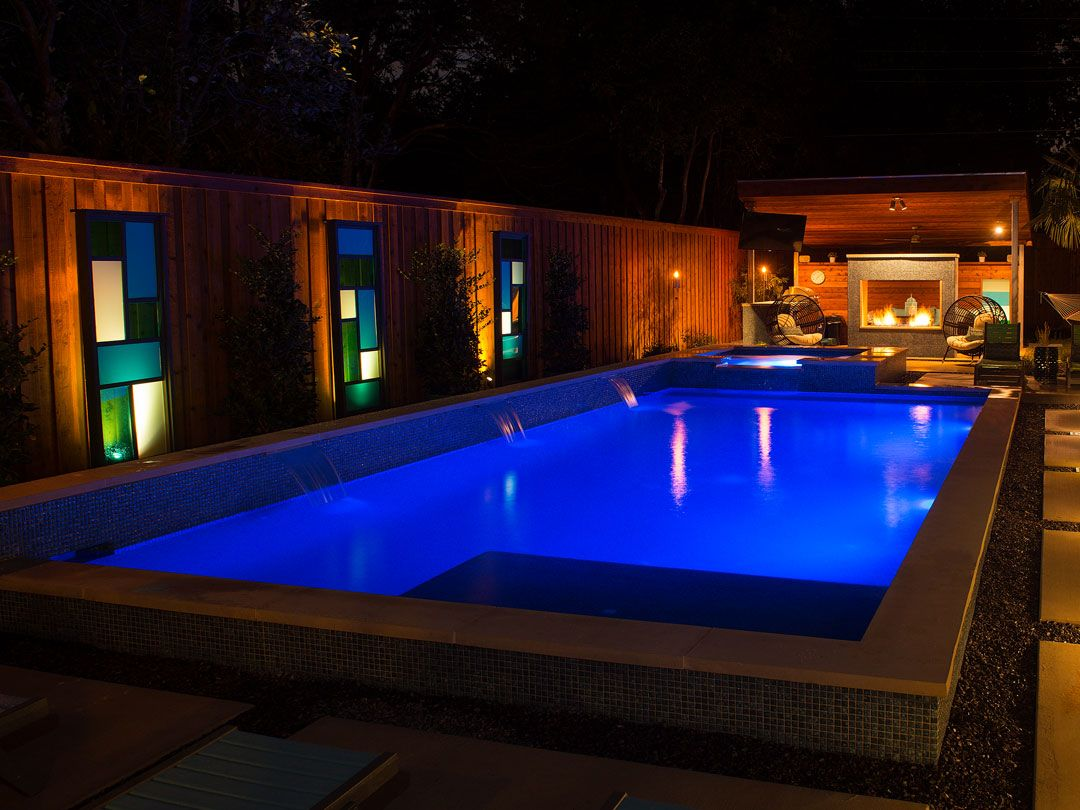 This image illustrates how striking and beautiful this backyard can become at night. As the daylight fades, this backyard is transformed into an entirely new space with gorgeous ambiance and comforting hues to entertain all. Truly a sight to see!