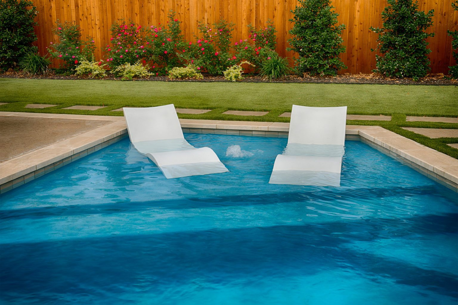 This image shows one of our favorite accessory pieces for swimming pools - Ledge Loungers! These pieces of pool furniture are water proof, stable and perfect add-on pieces for any splash pad. It gives the swimmer a perfect place to cool off, read a book or even enjoy a nice glass of iced tea while catching some rays!