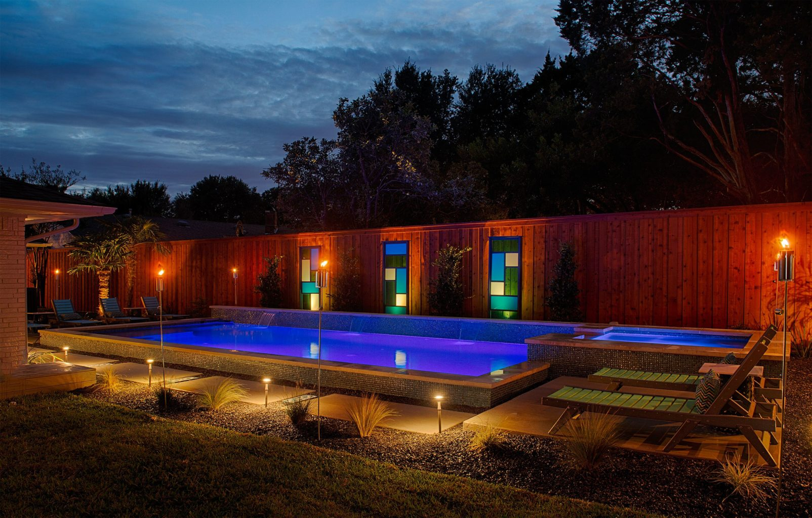 This is an image of the completed St. Albans project. This image is taken at night and shows the luminosity of this creative landscaping. We give kudos to our customers for accessorizing this pool with some beautiful glass piers and complimentary outdoor furniture.