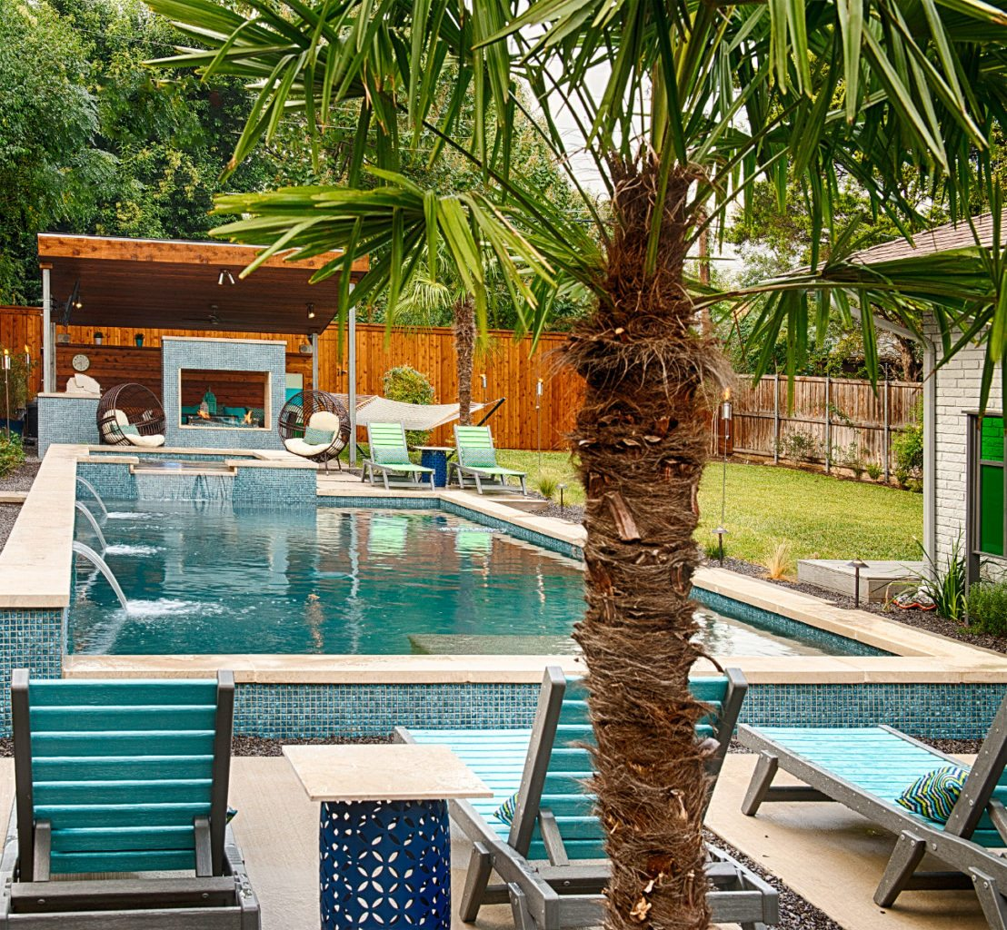 This pool provides amazing views from every angle. This image shows off a relaxing viewpoint of the outdoor kitchen and fire pit from the opposite. This palm tree is a great tool to provide shade from the heat of summer and gives your guests another place to relax during outdoor events.